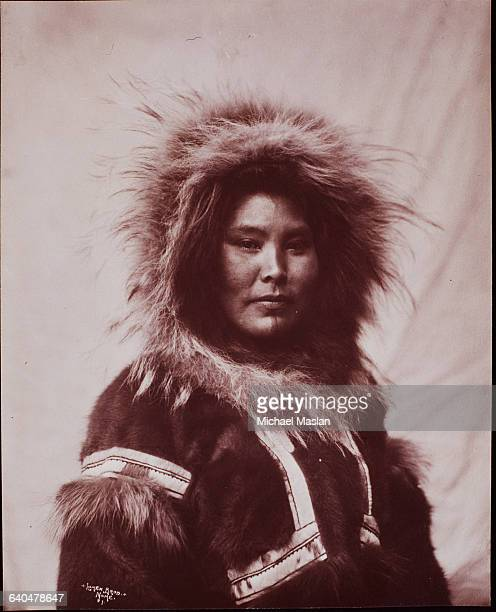 Portrait of an Eskimo woman, her face framed by the fur of a thick, warm parka.