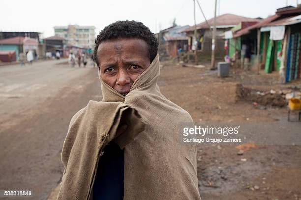Portrait of an Ethiopian man wrapped in a blanket with a cross tattooed on his forehead begging for food on a street of Debark Amhara Region Ethiopia