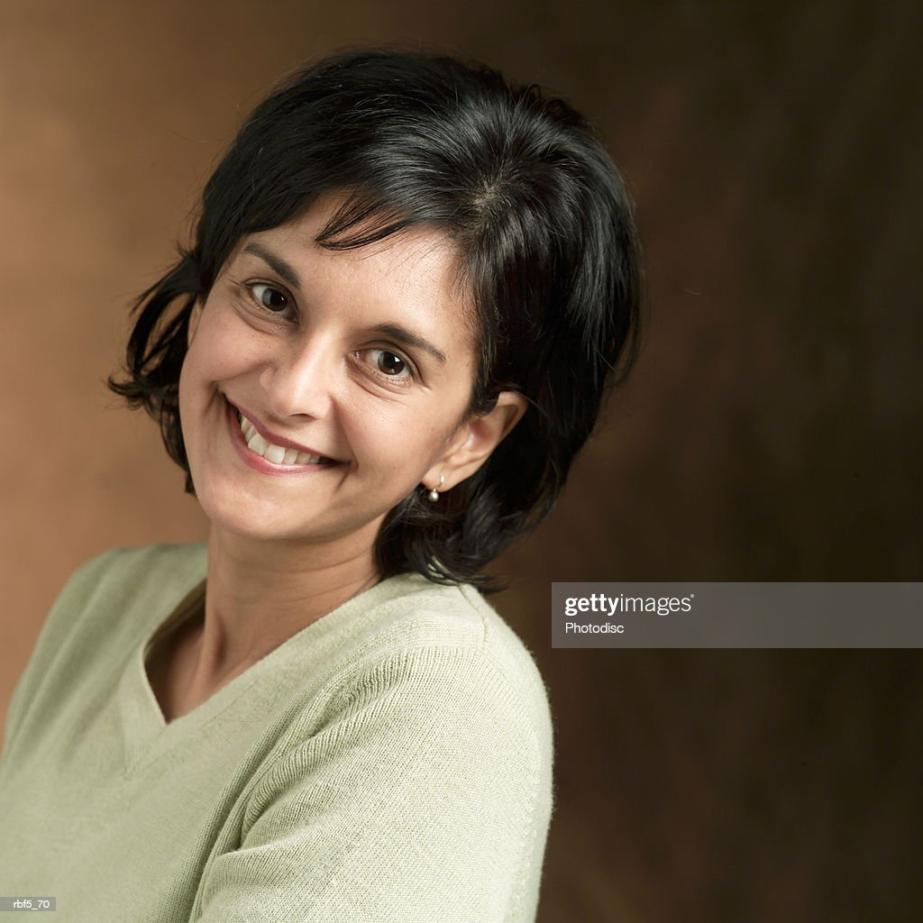 portrait of an ethnic looking woman in a tan sweater leans back and smiles into the camera : Stockfoto