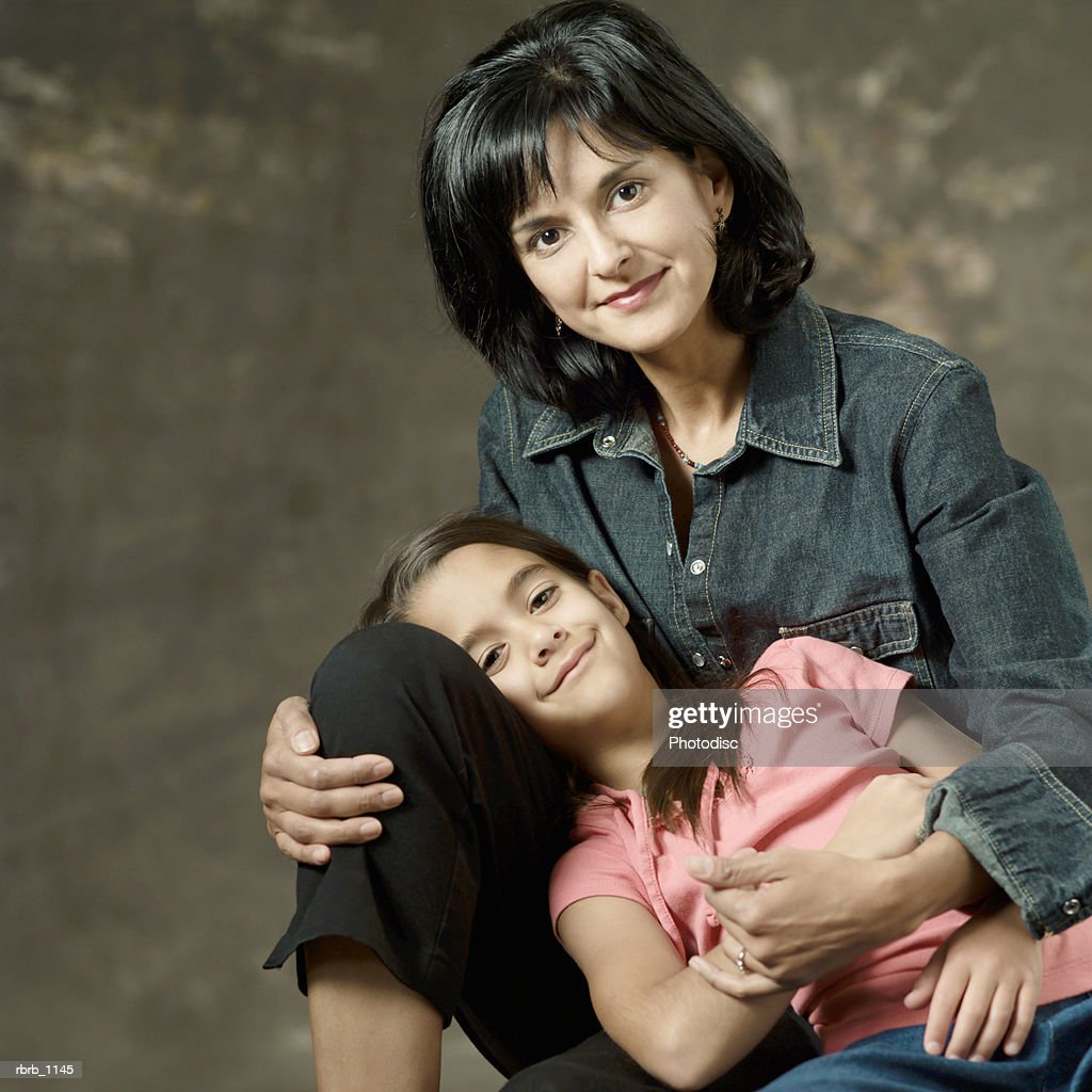 portrait of an ethnic mother and daughter as the child lays across her mothers lap : Stockfoto