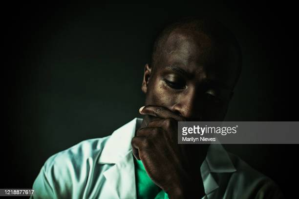 """portrait of an exhausted doctor with eye closed, hand on mouth - """"marilyn nieves"""" stock pictures, royalty-free photos & images"""