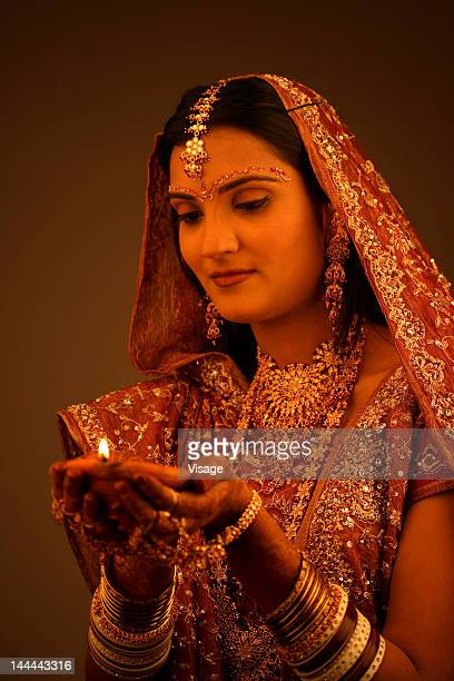 Portrait of an Indian bride holding a oil lamp