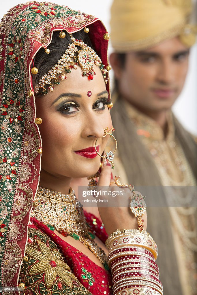 Portrait of an Indian bride posing with her husband in background : Stock Photo