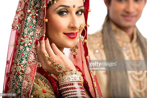 Portrait of an Indian bride posing with her husband in background