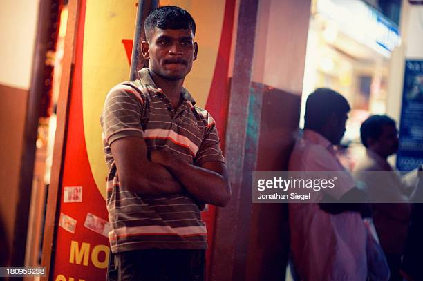 Portrait of an Indian man waiting for his friends in Little India, Singapore. Every Sunday the men who work in construction gather in Little India to...