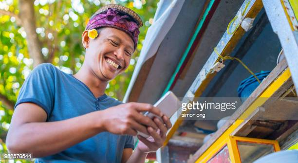 portrait of an indonesian young man smiling while using phone - indonesia stock photos and pictures