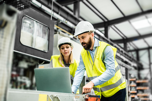 A portrait of an industrial man and woman engineer with laptop in a factory, working. 1046039246