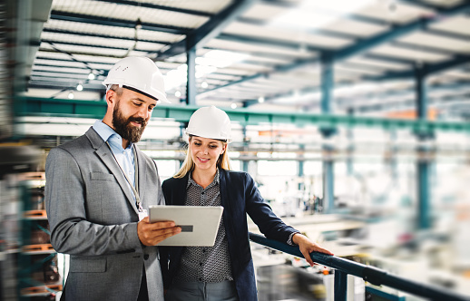 A portrait of an industrial man and woman engineer with tablet in a factory, working. 1059971802