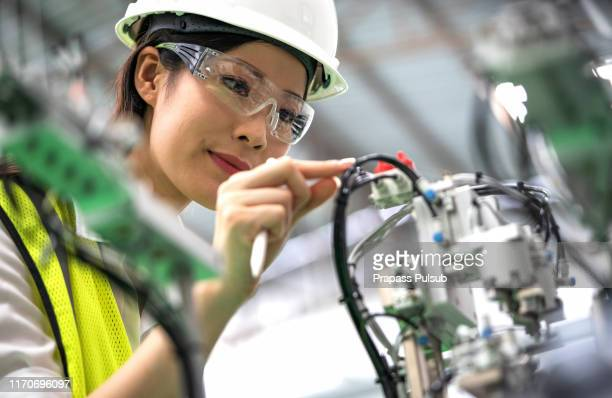 a portrait of an industrial woman engineer standing in a factory, arms crossed - design professional stock pictures, royalty-free photos & images
