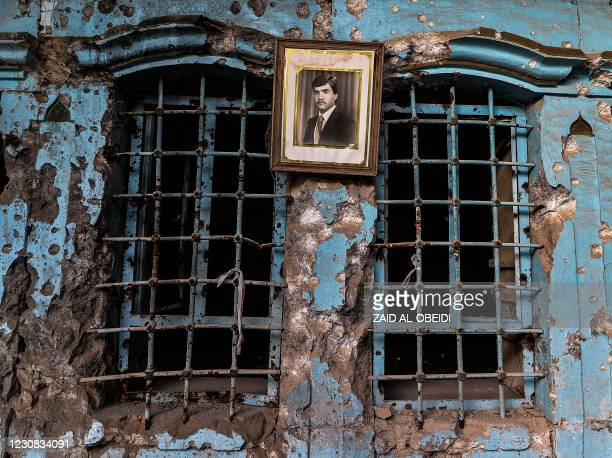 Portrait of an Iraqi Kurdish man hangs on the wall of his family's heavily damaged house in the Old City of Mosul on January 26, 2021. - Once the...