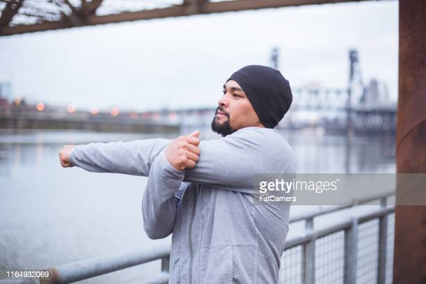 portrait of an ethnic male stretching out on a city bridge - goatee stock pictures, royalty-free photos & images