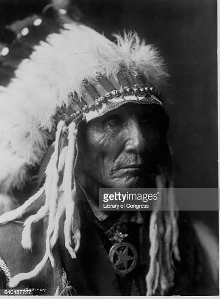 A portrait of an Oglala man wearing a feather bonnet trimmed in ermine published in Volume III of The North American Indian by Edward S Curtis