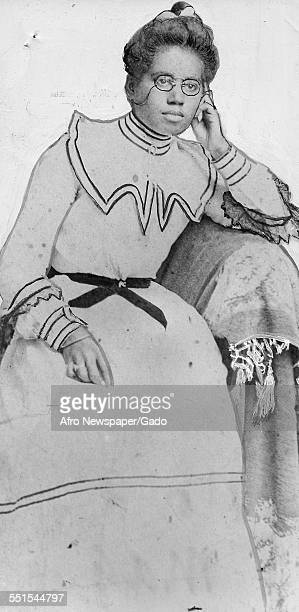 Portrait of an old AfricanAmerican woman in a long formal dress seated with her hair up 1909