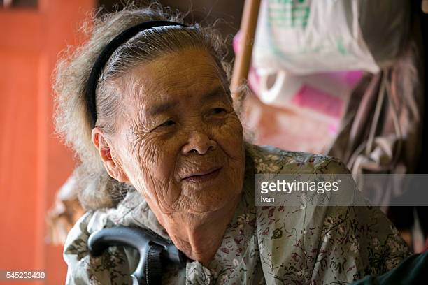 Portrait of An Old Asian Grandma Looking Left with Crutch