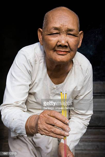 Portrait of an old Buddhist nun in a white dress offering smoking incense sticks in the door of Bayon temple, Angkor Wat, Siemp Reap Province,...