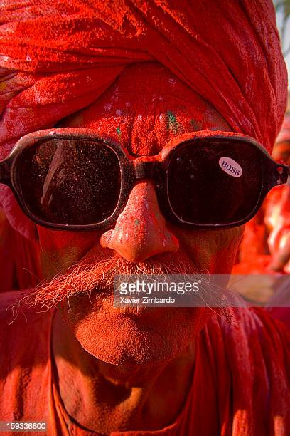 Portrait of an old man covered with coloured powdered dye and coloured water that people throw on each other during Holi the merriest of all the...