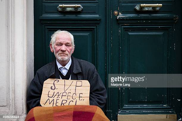 Portrait of an old man from Romania begging for coins in a street of Paris, France.