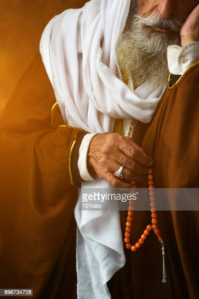 a portrait of an old middle eastern culture man and his rosary. - rosary beads stock pictures, royalty-free photos & images