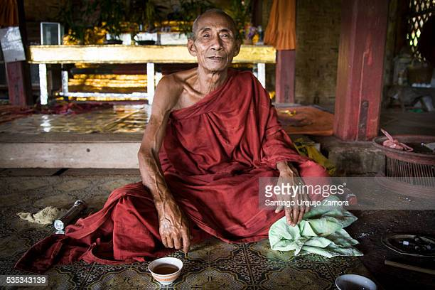 Portrait of an old serene Buddhist monk having a cup of tea at his monastery Hsipaw Shan State Myanmar Asia