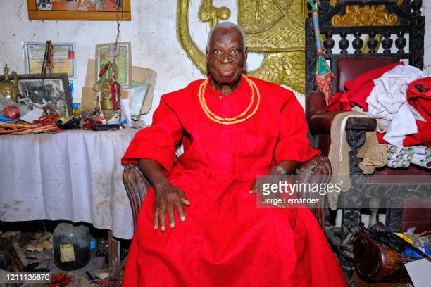 Portrait of an old traditional priest with various fetishes and amulets in his Benin City home