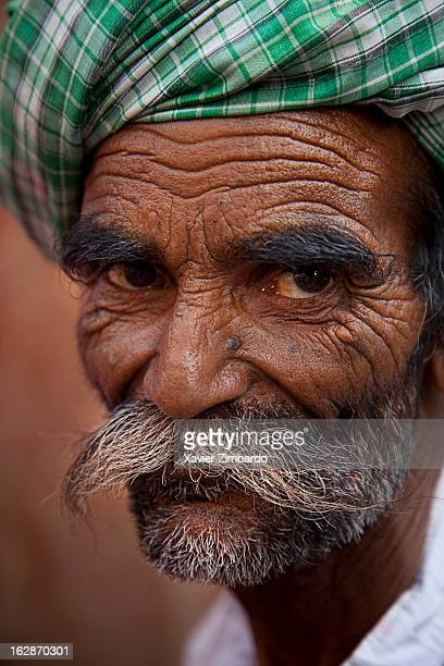 Portrait of an old worker wearing a turban and a big mustache on April 5 2009 inside a textile factory Rajasthan India