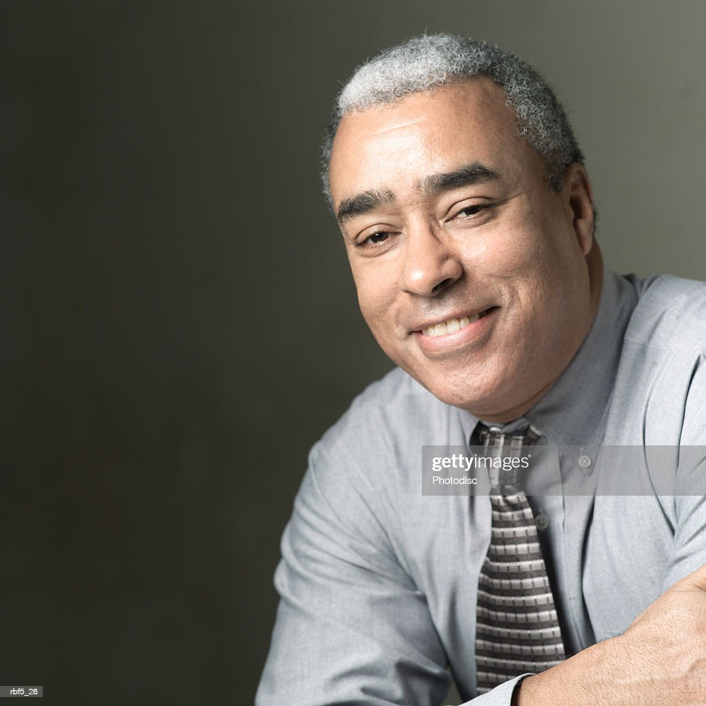 portrait of an older african american man in a grey shirt and tie as he folds his arms and smiles : Stockfoto