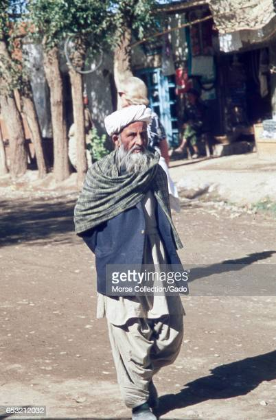 Portrait of an older man in traditional dress walking through the town square in Bamiyan located in the Hazarajat region of central Afghanistan...