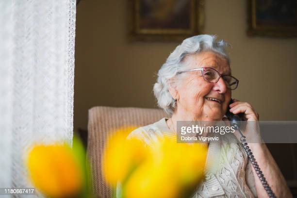 portrait of an older woman talking with the phone - grandmother stock pictures, royalty-free photos & images