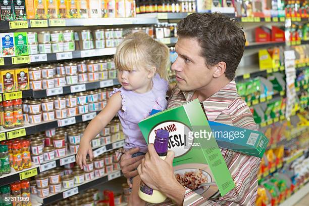 portrait of an overloaded father carrying his daughter whilst grocery shopping - struggle stock pictures, royalty-free photos & images