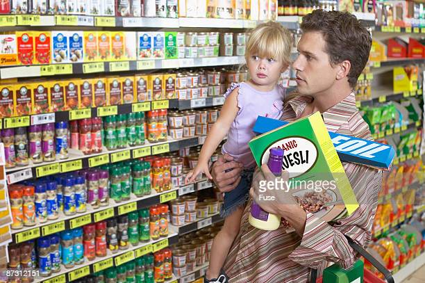 Portrait of an overloaded father carrying his daughter whilst grocery shopping