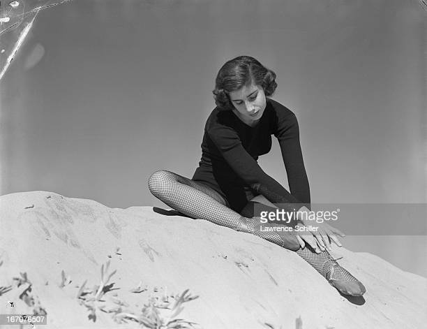 Portrait of an unidentified ballerina dressed in a leotard fishnet stockings and ballet slipper as she sits upon a pile of sand 1952