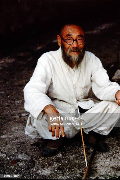 Portrait of an unidentified bearded man dressed in white as he crouches down a long pipe in his lap South Korea January 1952