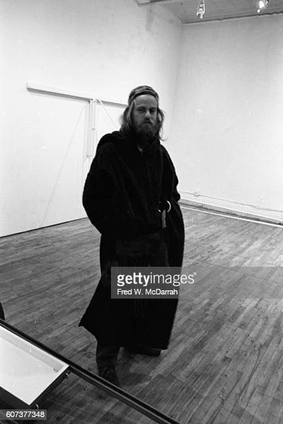 Portrait of an unidentified bearded man in an overcoat as he stands hands in his pockets in the Paula Cooper Gallery New York New York January 23 1971