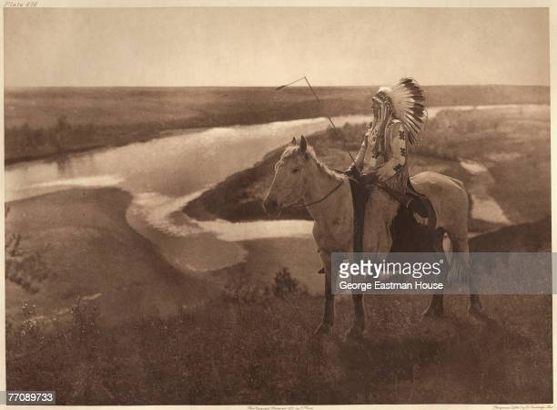 Portrait of an unidentified Blackfoot chief as he sits astride a horse on a hillside overlooking an unidentified body of water late 1800s or early...