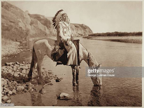 Portrait of an unidentified Blackfoot chief as he sits astride a horse who drinks from the Bow River Alberta Canada late 1800s or early 1900s