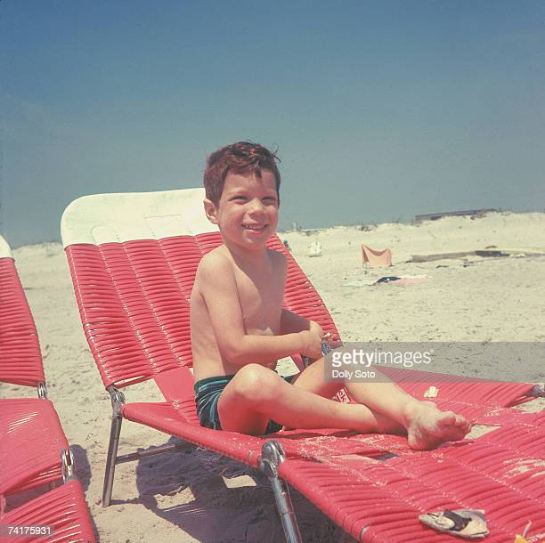 Portrait of an unidentified boy in swimming trunks as he sits on a deckchair on the beach at Fire Island New York August 1965 He holds a box of...