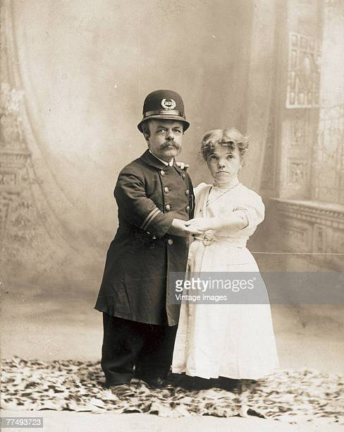 Portrait of an unidentified couple as they hold hands in a photographic studio Boonton New Jersey late 1800s Both dwarves the man is dressed in a...
