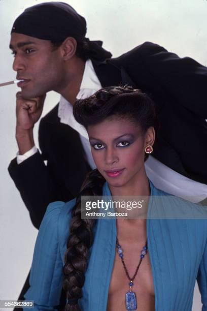 Portrait of an unidentified couple as they model against a white background New York 1980s He is smoking while wearing a dark blazer white button...