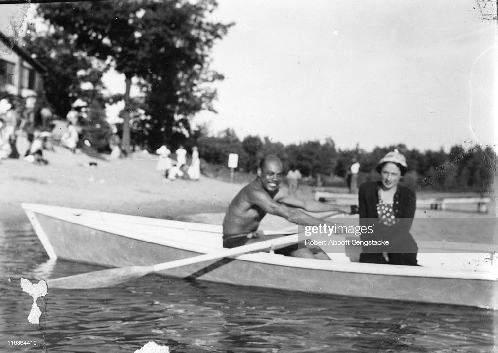 Portrait of an unidentified couple (friends and/or family members of future newspaper publisher John H. Sengstacke) in a rowboat near the shore of Idlewild Lake, Idlewild, Michigan, September 1938. Idlewild, known as 'the Black Eden,' was a resort community that catered to African Americans, who were excluded from other resorts prior to the passage of the Civil RIghts Act of 1964.