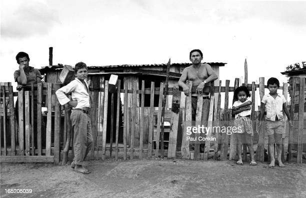 Portrait of an unidentified family as they pose in front of their home in one of the slum satellite cities that surround the capital Brasilia Brazil...