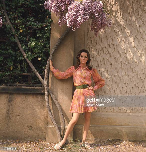 Portrait of an unidentified fashion model dressed in a pleated paisleypatterned pink skirt matching blouse and a green belt as she poses under a...