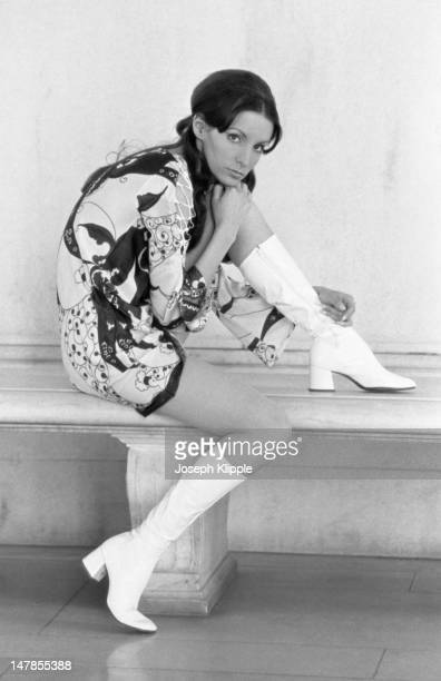 Portrait of an unidentified fashion model in a print mini dress and white plastic boots as she poses seated on a stone bench with her chin on her...