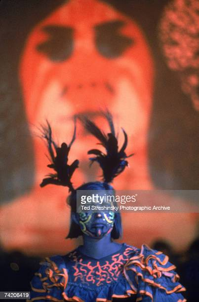 Portrait of an unidentified female dancer decorated in fluorescent body paint and with feathers in her hair as she attends an event at the Avalon...