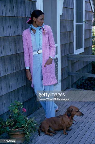 Portrait of an unidentified female model as she poses with a Dachshund on the porch of a house dressed in a fulllength pink cableknit cardigan and...