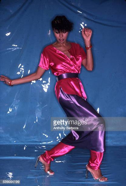 Portrait of an unidentified female model in a pink satin top and a purple skirt over pink trousers as she poses in front of a lightblue colored...