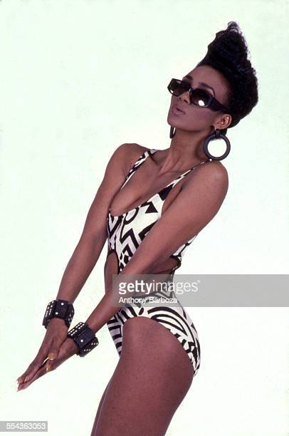 Portrait of an unidentified female model wearing a bathing suit with black and white geometric shapes sunglasses and oversize earrings and bracelets...