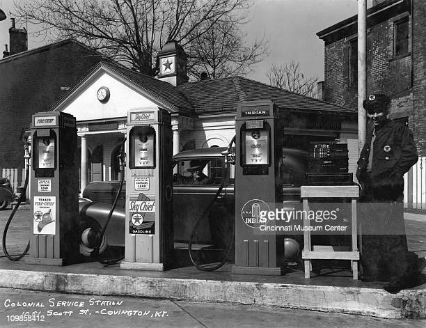 Portrait of an unidentified gas station attendant at the Texaco Colonial Service Station who smiles and stands with his pockets as a customer in a...