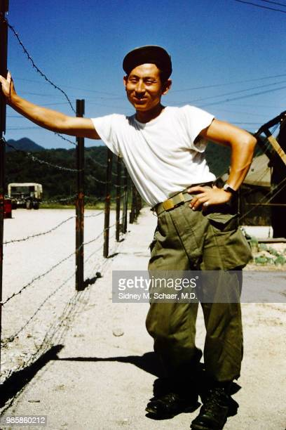 Portrait of an unidentified man dressed in a tshirt and wearing militaryissue trousers as he leans on a barbed wire fence at the 8063rd MASH South...