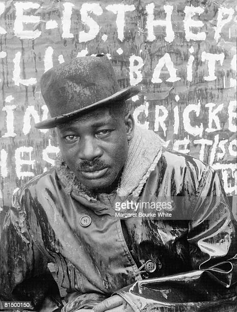 Portrait of an unidentified man in a wet rain slicker and a hat as he works at a bait shop in the rain Augusta Georgia 1937