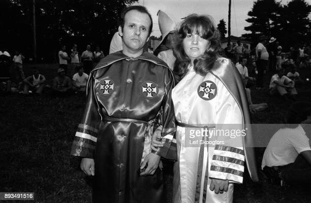 Portrait of an unidentified, married couple, both members of the American racist, terrorist organization the Ku Klux Klan , both dressed in the...